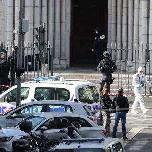 Poliser och polisbilar vid ingången till en kyrka.