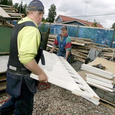 Män bär byggmaterial vid husbygge.