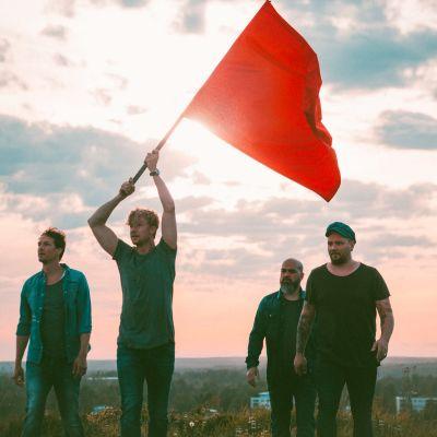 Sunrise Avenue kävelee auringonlaskussa ja Samu Haber kantaa punaista lippua.
