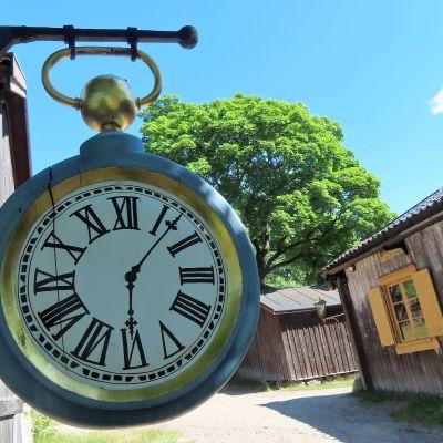 En klocka hänger utanför en vägg på Klosterbacken i Åbo.