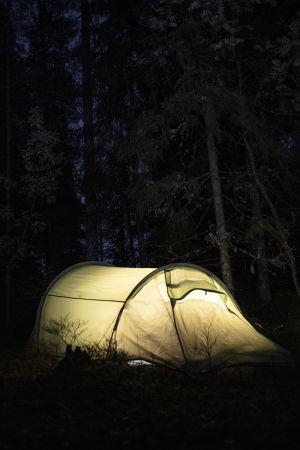 Valaistu teltta pimeässä metsässä.