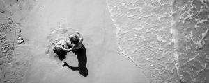Lekande pojke på stranden.
