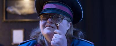 En person klädd som en museivakt kikar mot kameran genom ett förstoringsglas.