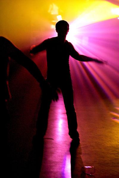 Tanssi. Mies tanssii tanssilattialla, värivalot. Disco. Siluetti.
