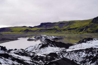 Glaciär i förgrunden, gröna berg i bakgrunden.