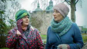 Kaksi naista seisoo syksyisessä maisemassa