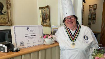 Ulla Liukkonen seisomassa vierellään kunniakirja