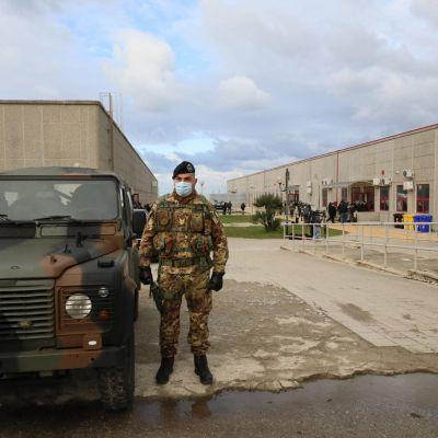 Sotilas seisoo maastokuvioisessa univormussa maastokuvioiden jeepin vieressä. Takana näkyy kaksi betoninharmaata rakennusta.