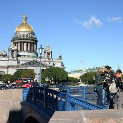 Matkailijoita sinisellä sillalla Iisakinkirkon edessä.
