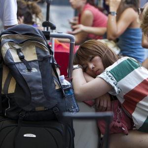 Naismatkailija istuu ja nojaa matkatavaroihinsa silmät ummessa, ympärillä muita istuvia matkailijoita.