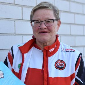 Marja-Liisa Lehto står med Karis Uras 90-års historik i händerna.