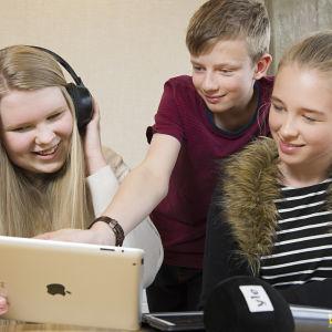 Kolme lasta katsoo tabletista Triplet-palvelua.