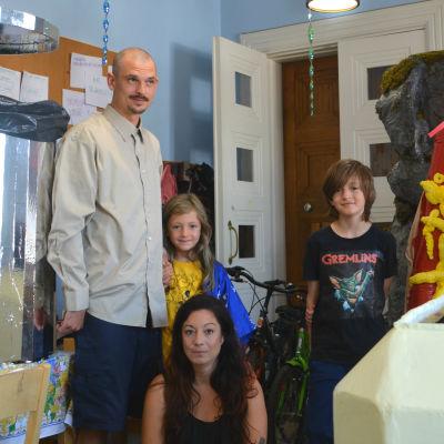 En kvinna sitter på huk mellan en man och två barn som står i ett rum mitt emellan två konstverk.