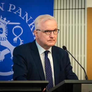 Chefen för Finlands Bank Olli Rehn står och talar framför en mikrofon.