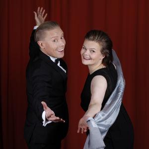 Nicke Aldén och Silja Sahlgren-Fodstad poserar framför en röd ridå.