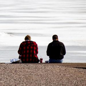 Kaksi henkilö syö lounasta laiturilla talvisessa maisemassa.