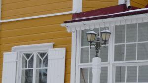 detaljer på fasden på Villa Snäcksund, lite glasveranda, fönster med vita luckor, gul brädfodring