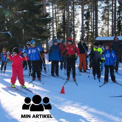 Flera personer, främst unga, på längdskidor i strålande vinterväder.
