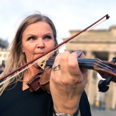 Raakel Lignell soittaa viulua Berliinin muurilla, Brandenburgin portin edessä
