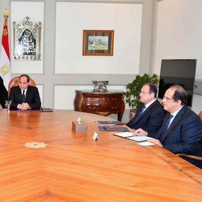 Presidentti ja ministerit istuvat suuren pöydän ääressä neuvonpidossa.