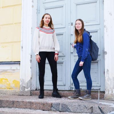 Två unga kvinnor står på trappan till Lovisa Gymnasium, ett gult trähus med blå ytterdörr. Den ena av dem håller i dörrhandtaget.