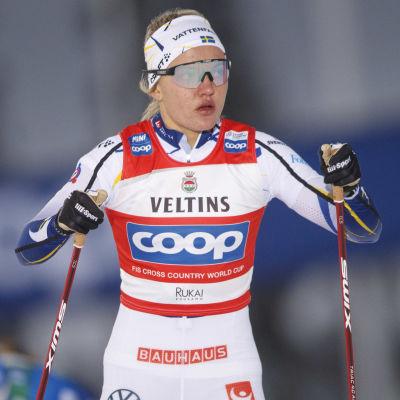 Linn Svahn blickar bekymrat åt sidan med stavarna i händerna.