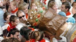 Väenpaljoutta ja lapsia, jotka katsovat ja koskettavat Pamplonan jättiläispatsaan päätä.