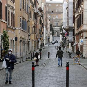 Muutama ihminen lähes tyhjälla kadulla.