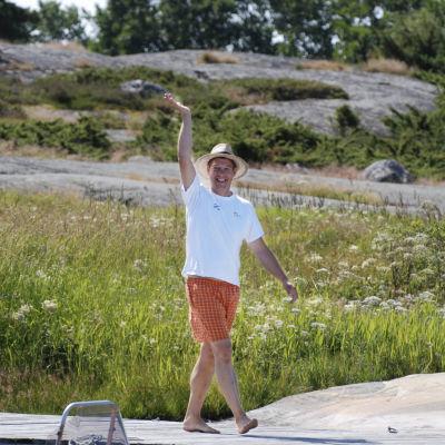 Riko Eklundh går på en brygga och vinkar. Han har orangerutiga shorts, vit t-skjorta och en halmhatt på sig.