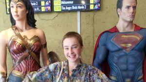 Veera Lapinkoski poserar framför superhjältar i biofoajé.