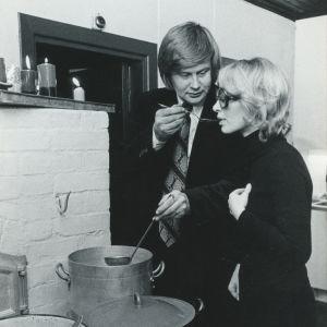Kirjailijapariskunta Kai Linnilä ja Kaari Utrio keittiöässään kattiloiden ääressä maistelemassa soppaa.