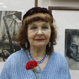 Margarita Izotova står framför Marttila-tavlor. Enligt Margarita Izotova skapar de sköna verken en stark själ.