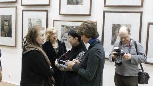 Folk diskuterar under en utställning med Jelena Marttilas konst.