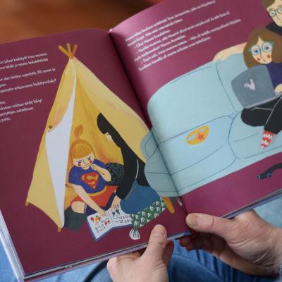 En person läser boken Ihmeellinen Minna ja suomalaiset supernaiset av Elina Lappalainen.