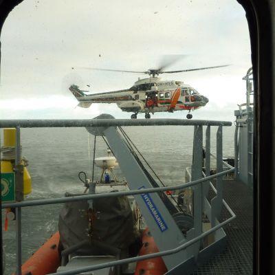 Helikopter kommer för att lämna över den nödställde till Sjöbevakningens fartyg.