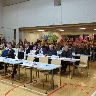 Sjundeå fullmäktige beslutar om Sjundeås framtid. I bakgrunden åhörare.