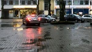En taxibil och några andra bilar på ett regnigt gatu- och parkeringsområde i Ekenäs en novemberdag.