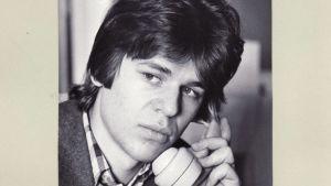 En ung Martin Scheinin sitter med en telefonlur i handen i slutet av 70-talet.