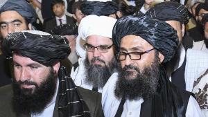 Talibanernas förhandlare som leds av mulla Abdul Ghani Baradar (till höger) undertecknade fredsavtalet med USA i februari i Qatar.