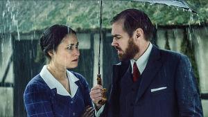 Fie och Morten under ett paraply i ösregn.
