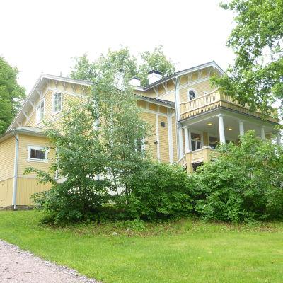 En gul stor träbyggnad som är omgiven av lummiga träd och buskar.