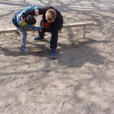 två barn kämpar på en bänk
