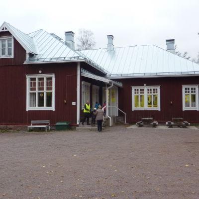 Ett rött trähus ute på landsbygden. Det är Västankvarns skola i Ingå.