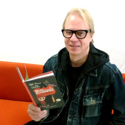Författaren Peter Sandström sitter i en röd soffa och håller i sin bok Rööluuvån.