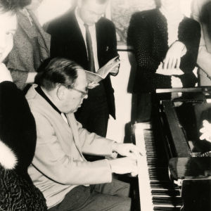 Pianotaiteilja Gerald Moore soittaa opiskelijoiden ympäröimänä.