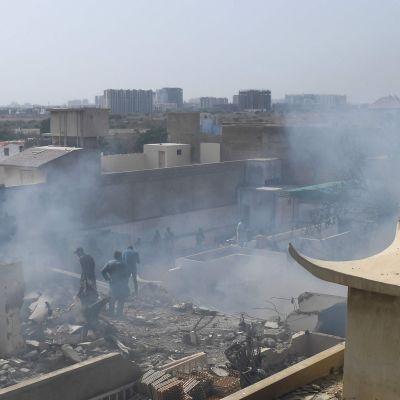 Rök och eventuellt damm i luften efter en flygkrasch i ett bostadsområde i Karachi den 22 maj.
