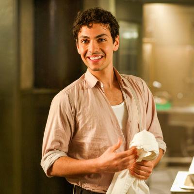 Karaktären Angelo står i köket och torkar sina händer.