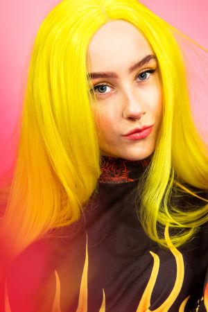 Keltahiuksinen nuori nainen katsoo vino hymy kasvoillaan kameraan, päällä liekkikuvioinen paita.