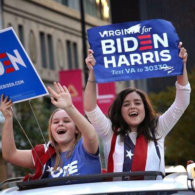 Kaksi iloista naista on kurottelee auton kattoikkunasta ja pitää Biden-Harris kylttejä.