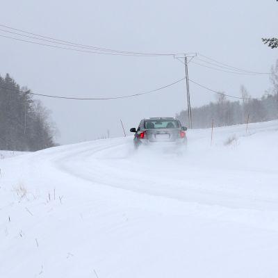 En bil kör in i en kurva på en snöig väg.